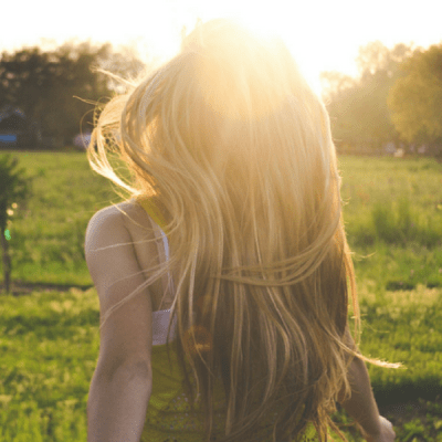 A person with long blonde hair looking out into the distance as a sunset peaks over the trees in the background.